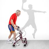 Hope for the future. Sick old man walking with a walker along with a shadow of a young athlete on the wall. Concept for youth passing like a shadow or hope for Royalty Free Stock Image