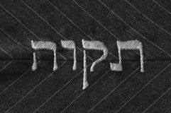 Hope in Hebrew language, stitched on fabric -  monochrome. Hebrew word 'tikvah' (meaning 'hope' in english) satin stitched on a pinstripe background. Black and Stock Images