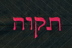 Hope in Hebrew language, stitched on fabric. Hebrew word 'tikvah' (meaning 'hope' in english) satin stitched in hot pink against a charcoal gray, pinstripe Stock Photos