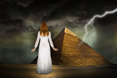 Hope, Inspiration, Beautiful Woman, Lightning. Abstract scene for hope and inspiration. A young beautiful redhead woman is looking at the great pyramid of Giza Royalty Free Stock Image