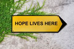 Hope lives here on yellow sign hanging on ivy wall Stock Photos