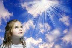Hope for miracles. A girl with eager and smiling expression looking toward rays of divine Royalty Free Stock Image