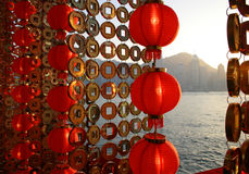 Hope for Prosperity. Red lanterns and gold coins as part of the Chinese New Year decorations in Hong Kong, with skyscrapers across the harbor Stock Image