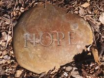 HOPE Rock. While walking around the neighborhood...I spotted something from the corner of my eye. A rock with one, inspired word stock photo