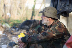Hope. Slovenly homeless man with a burning cigarette hopes a better year Royalty Free Stock Photos