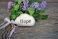 Hope on stone with lilacs Royalty Free Stock Image