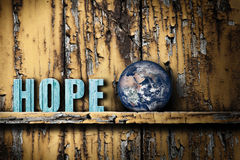 Hope text word and planet Earth on worn wooden background. Word text hope and planet Earth on the shelf on worn wooden background. Concept of hope for the health Royalty Free Stock Photography