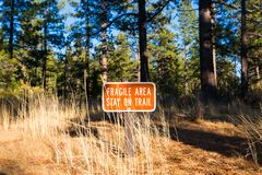 Hope Valley, California, United States. `Fragile Area - Stay on Trail` red sign near the forest trail. Hope Valley, California, United States royalty free stock photos