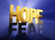 Hope Vanquishes Fear. Viewed at a dramatic angle, a shiny, gold HOPE stands atop a dark gray FEAR on a deep blue background brilliantly back lit with light rays Stock Photo