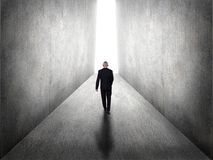 Hope Vision in Business Concept. Rear view of a businessman walking to bright light from darkness stock image