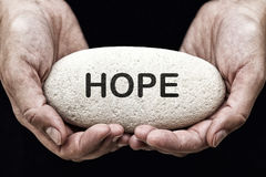 Hope. Woman's hands hold stone with word Hope Royalty Free Stock Images