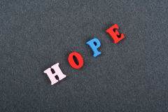 HOPE word on black board background composed from colorful abc alphabet block wooden letters, copy space for ad text Royalty Free Stock Images