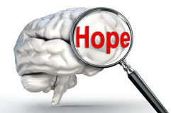 Hope word on magnifying glass and human brain Stock Image