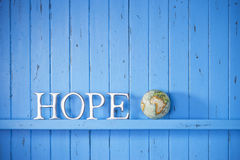 Hope World Globe Background. A blue painted wood background with the word hope on it with a world globe royalty free stock photo