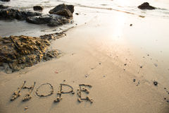 Hope written in the sand at the beach waves in the background Royalty Free Stock Photo