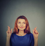 Hopeful beautiful woman crossing her fingers, eyes closed, hoping Royalty Free Stock Images