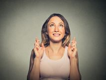 Hopeful beautiful woman crossing her fingers looking up hoping Royalty Free Stock Photography