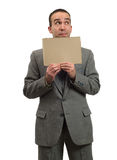 Hopeful Businessman. A young businessman hopeful about the economy is holding a blank cardboard sign, isolated against a white background Royalty Free Stock Photo