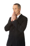 Hopeful businessman with clenched hands Royalty Free Stock Image