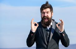Hopeful and confident about future. Alright gesturing. Man bearded optimistic businessman wear formal suit sky stock image
