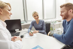 Hopeful consultation from female medical adviser. Happy smiling couple is sitting afore kind doctor. She looking at patients with smile Stock Photography