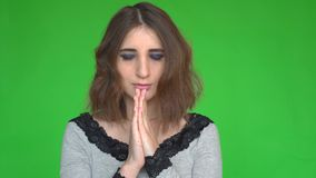 Hopeful female keeps hands together in praying gesture over green background. Posing against a removable chroma key background. Concept of emotions stock video footage