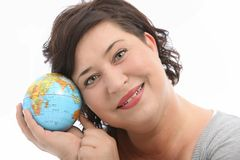 Hopeful female tourist. Smiling woman holds a world globe close to her head as she dreams of going on a long vacation sightseeing to worlwide destinations Royalty Free Stock Photography