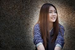 Hopeful girl. A beautiful Asian (Thai) girl is sitting in the light against a dark background with a hopeful expression Stock Images