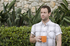 Hopeful man with a coffee mug. Hopeful man outdoors holding an orange coffee mug looking out to the side Royalty Free Stock Image