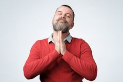 Hopeful man join hands in prayer asking for help. Hopeful mature caucasian man in red sweater join hands in prayer thanking asking for best. Husband praying or royalty free stock photos