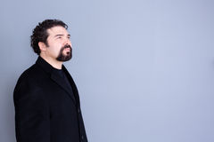 Hopeful man looking away over gray background. Three quarter view of hopeful attractive dark haired and bearded middle aged male in black shirt and blazer Stock Photos