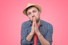 Hopeful man in summer hat join hands in prayer thanking asking for best. On pink wall, Studio shot royalty free stock image
