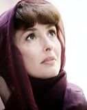 Hopeful mature woman. In a scarf looking up Royalty Free Stock Photos