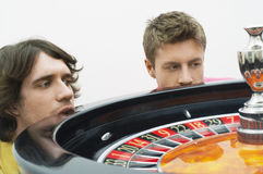 Hopeful Men Watching Roulette Wheel Spin. Closeup of two hopeful young men watching roulette wheel spin stock photo