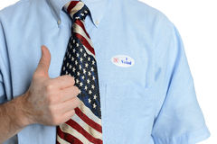 Hopeful Patriot Voter. Patriotic voter wearing a U.S. flag tie and dress shirt with an I voted sticker gives the thumbs up sign Royalty Free Stock Photography