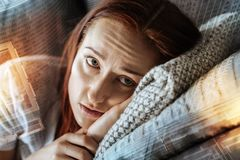 Hopeful sad woman looking aside and thinking. In anticipation. Hopeful sad pretty woman lying at home on the fofa looking aside and thinking Stock Photos