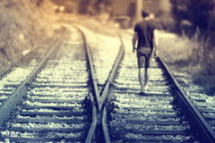 Hopeful walking on rails. A man walking alone down the railway tracks. Selective focus used. Hopeful walking on rails Royalty Free Stock Images