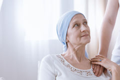 Hopeful woman after cancer treatment. Hopeful women after cancer treatment holding friend`s hand Royalty Free Stock Images