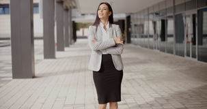 Hopeful woman with folded arms near building Royalty Free Stock Images
