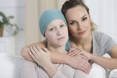 Hopeful woman hugging sad girl. Hopeful women hugging sad girl who just received a cancer relapse diagnosis Royalty Free Stock Photos