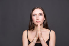 Hopeful woman with praying hands portrait. Attractive woman praying on dark background Royalty Free Stock Photo