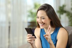 Hopeful woman waiting for online news in a smartphone. Sitting on a couch in the living room at home Stock Photos