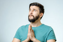 Hopeful young man praying. Over gray Royalty Free Stock Photography