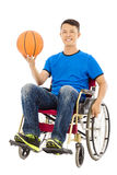 Hopeful young man sitting on a wheelchair with a basketball Stock Photography