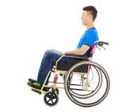 Hopeful young man sitting on a wheelchair in studio Stock Image