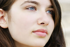 Hopeful young woman looking away. Portrait of s beautiful hopeful or pensive young woman with fair skin and light blue and green eyes, simple and natural Royalty Free Stock Images