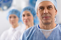 Hopefully smiling male medical person. Happy surgeon in surgical wear is looking ahead with inspiration and light smile. Portrait Royalty Free Stock Image