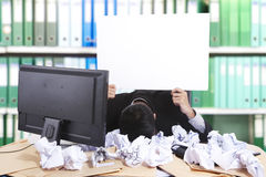 Hopeless businessman with blank banner. Hopeless businessman holding an empty board, shot in office with many waste paper Royalty Free Stock Photo
