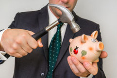 Hopeless businessman breaking piggy bank with hammer Stock Photography