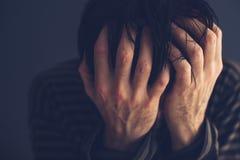 Hopeless drug addict holding his head stock image